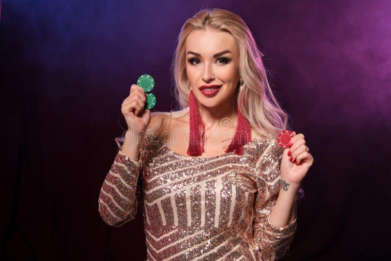 Den blonda kvinnan med en perfekt frisyr och ett ljust smink poserar med dobblerichiper i hennes händer Kasino poker royaltyfria foton