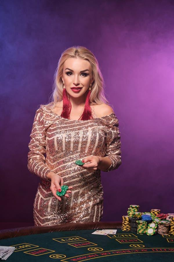 Den blonda kvinnan med en perfekt frisyr och ett ljust smink poserar med dobblerichiper i hennes händer Kasino poker fotografering för bildbyråer