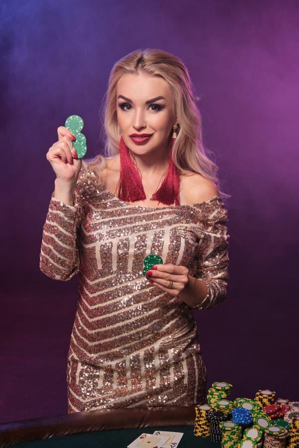Den blonda kvinnan med en perfekt frisyr och ett ljust smink poserar med dobblerichiper i hennes händer Kasino poker royaltyfri foto