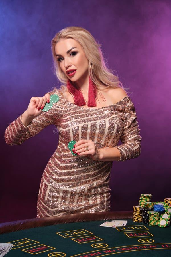 Den blonda kvinnan med en perfekt frisyr och ett ljust smink poserar med dobblerichiper i hennes händer Kasino poker arkivbild