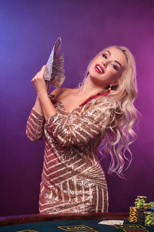 Den blonda kvinnan med en perfekt frisyr och ett ljust smink poserar med fanen av hundra dollarräkningar i hennes händer kasino arkivfoto