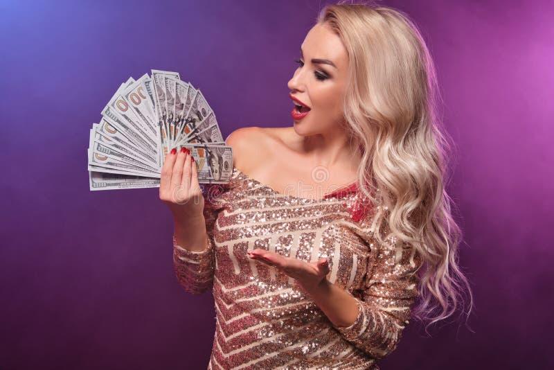 Den blonda kvinnan med en perfekt frisyr och ett ljust smink poserar med fanen av hundra dollarräkningar i hennes händer kasino royaltyfri fotografi