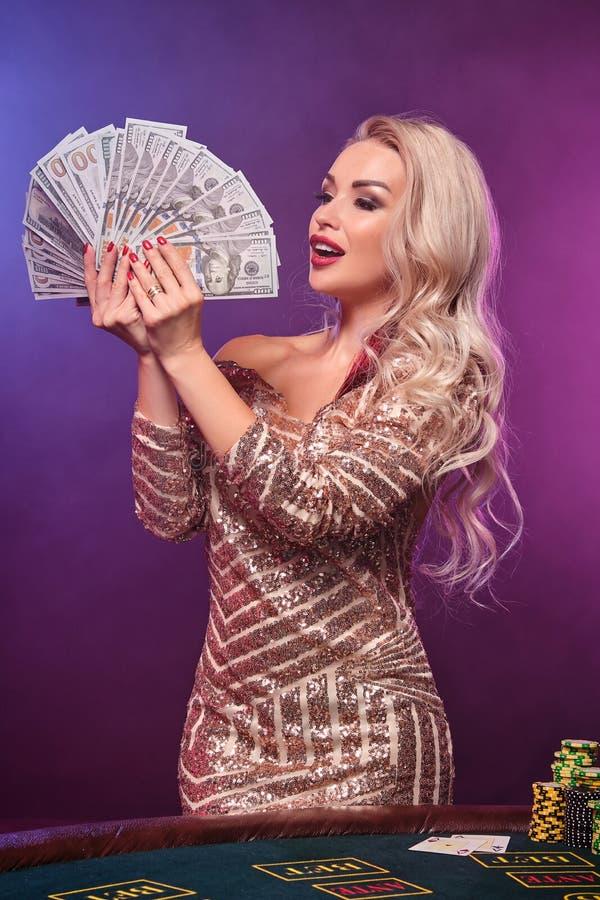Den blonda kvinnan med en perfekt frisyr och ett ljust smink poserar med fanen av hundra dollarräkningar i hennes händer kasino royaltyfria foton