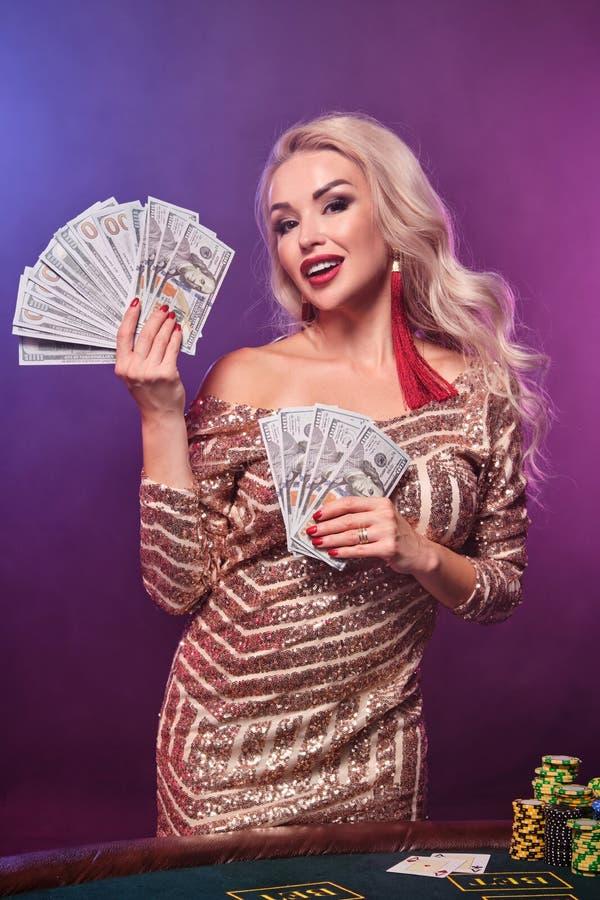Den blonda kvinnan med en perfekt frisyr och ett ljust smink poserar med fanen av hundra dollarräkningar i hennes händer kasino royaltyfri foto