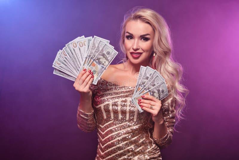 Den blonda kvinnan med en perfekt frisyr och ett ljust smink poserar med fanen av hundra dollarräkningar i hennes händer kasino arkivfoton