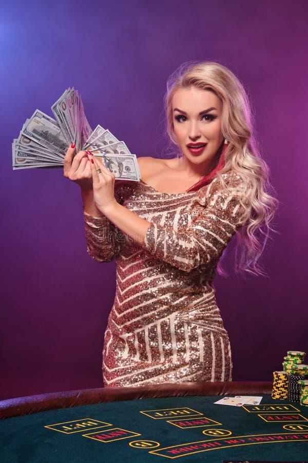 Den blonda kvinnan med en perfekt frisyr och ett ljust smink poserar med fanen av hundra dollarräkningar i hennes händer kasino royaltyfri bild