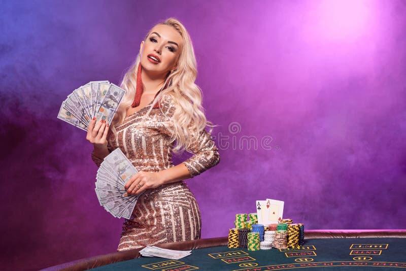 Den blonda kvinnan med en perfekt frisyr och ett ljust smink poserar med spela kort i hennes händer Kasino poker fotografering för bildbyråer