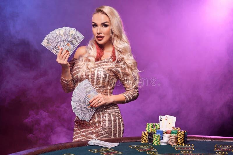 Den blonda kvinnan med en perfekt frisyr och ett ljust smink poserar med spela kort i hennes händer Kasino poker royaltyfri foto