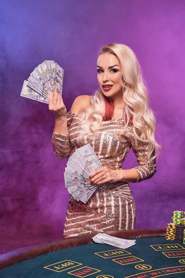 Den blonda kvinnan med en perfekt frisyr och ett ljust smink poserar med spela kort i hennes händer Kasino poker royaltyfria foton
