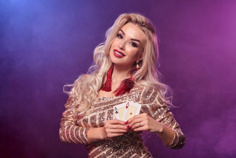 Den blonda kvinnan med en perfekt frisyr och ett ljust smink poserar med spela kort i hennes händer Kasino poker arkivbilder