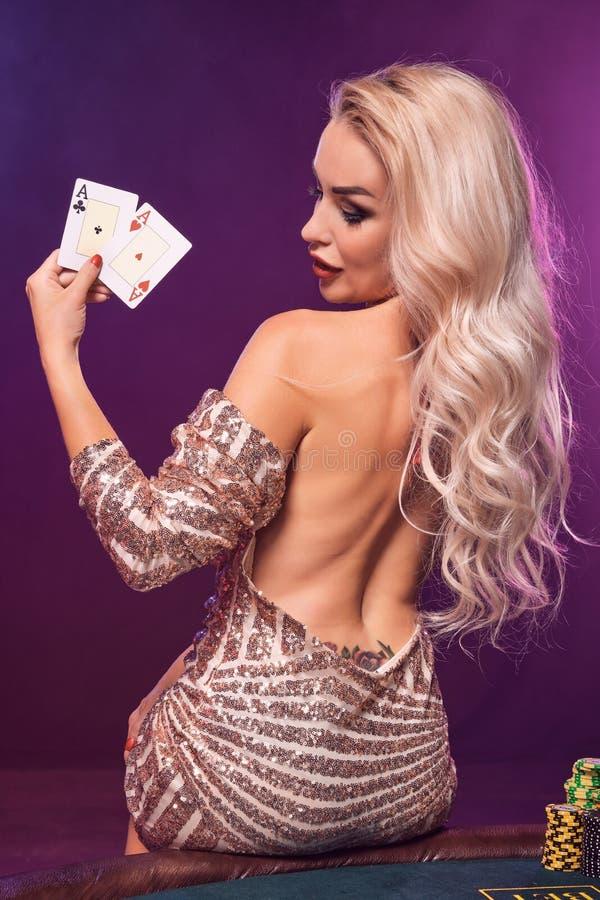 Den blonda kvinnan med en perfekt frisyr och ett ljust smink poserar med spela kort i hennes händer Kasino poker arkivfoton