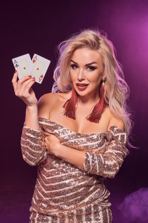 Den blonda kvinnan med en perfekt frisyr och ett ljust smink poserar med spela kort i hennes händer Kasino poker royaltyfri bild