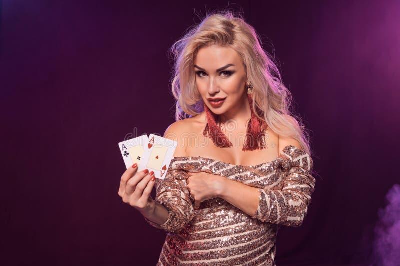 Den blonda kvinnan med en perfekt frisyr och ett ljust smink poserar med spela kort i hennes händer Kasino poker royaltyfri fotografi