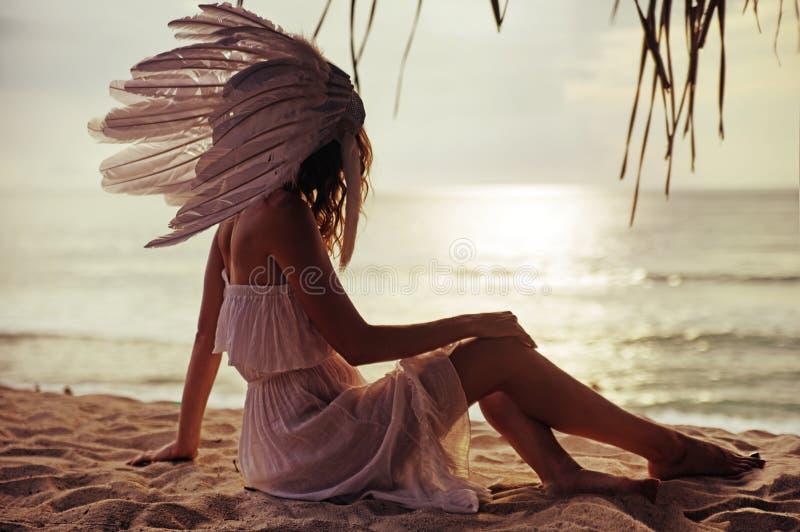 Den blonda kvinnan med ett enormt putsar att hålla ögonen på solnedgången royaltyfria bilder