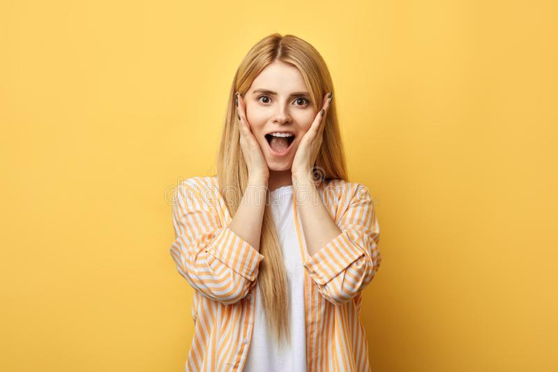 Den blonda kvinnan med gömma i handflatan på kinder, uttrycker hennes lycka royaltyfri foto