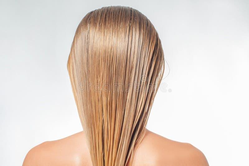 Den blonda kvinnan med länge vått hår applicerar hårhårbalsamen arkivfoton