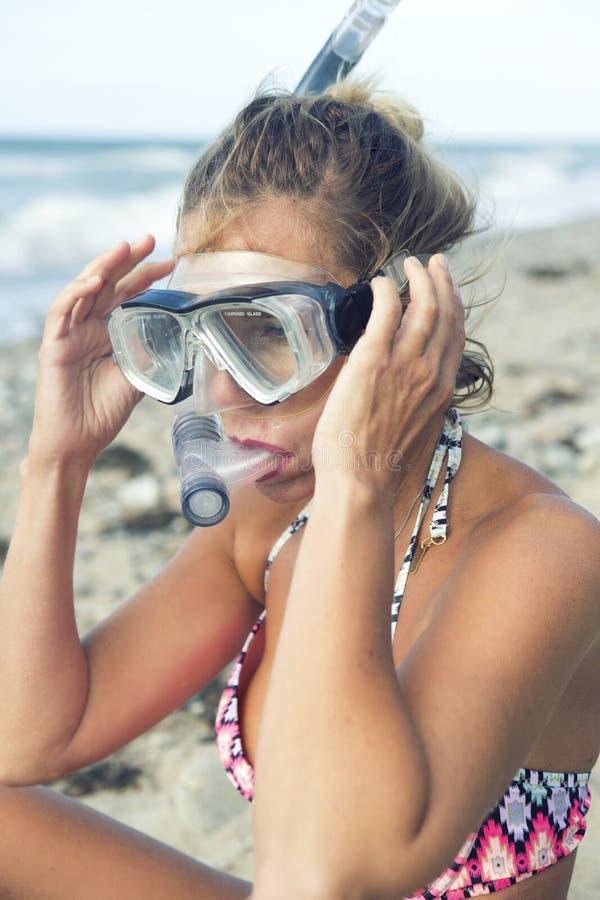 Den blonda kvinnan med simning rullar med ögonen på stranden royaltyfri bild