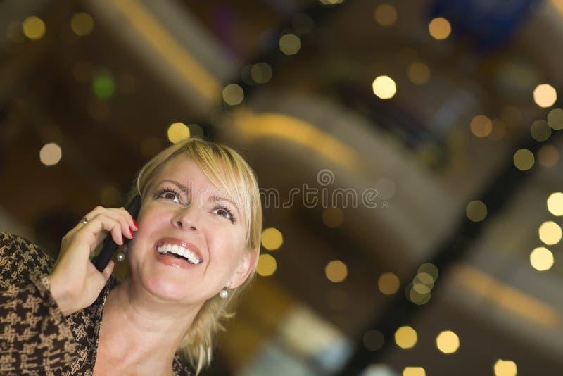 Den blonda kvinnan på som henne ringer cellen i staden tänder royaltyfria bilder