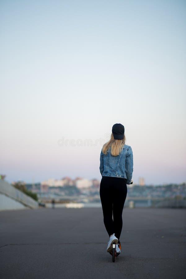 Den blonda kvinnan rider en sparkcykel i bakgrunden av staden royaltyfria foton