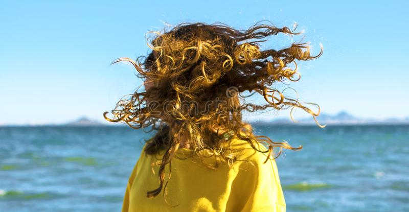 Den blonda kvinnan skakar huvudet med lockigt hår på stranden arkivfoto