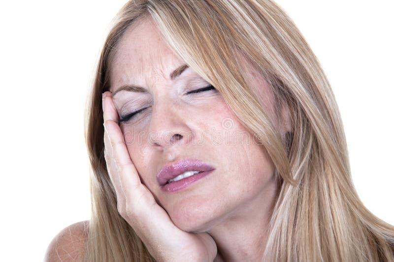 Den blonda kvinnan smärtar in har tandvärk arkivbild