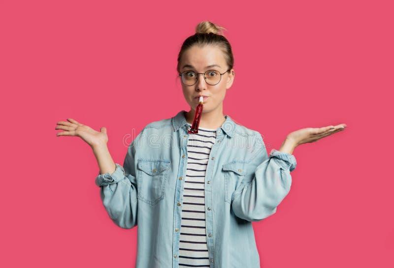 Den blonda kvinnan som har en födelsedag, blåser hon i partislaghorn fotografering för bildbyråer
