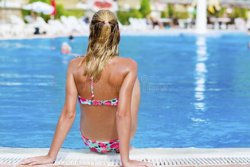 Den blonda kvinnan som tycker om sommarsemestern som lägger på, sunbed i en tropisk trädgård arkivbild