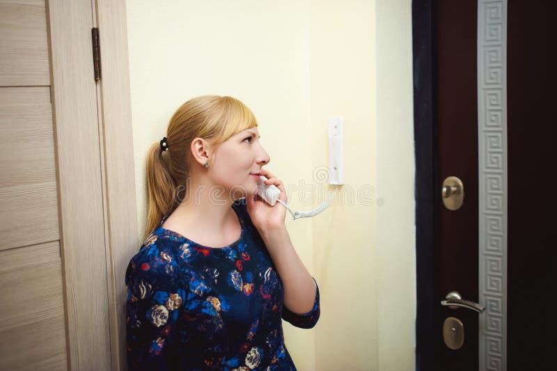 Den blonda kvinnan svarar högtalaranläggningappell, rymmer telefonen till hans öra arkivfoto