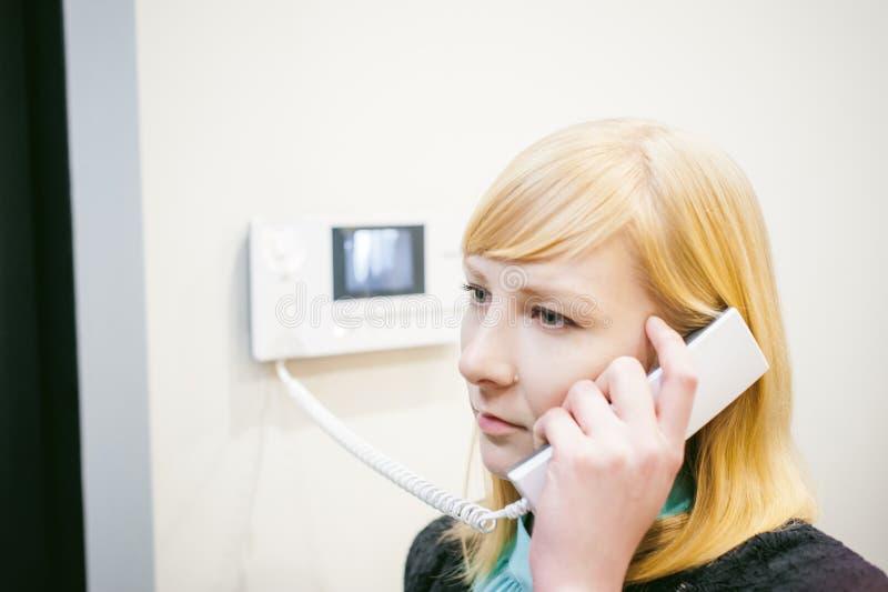 Den blonda kvinnan svarar högtalaranläggningappellen royaltyfri bild