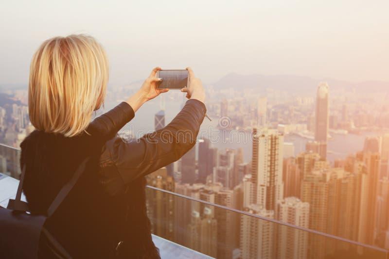 Den blonda kvinnliga handelsresanden gör fotoet med kameran för celltelefonen av det Kina landskapet arkivbilder