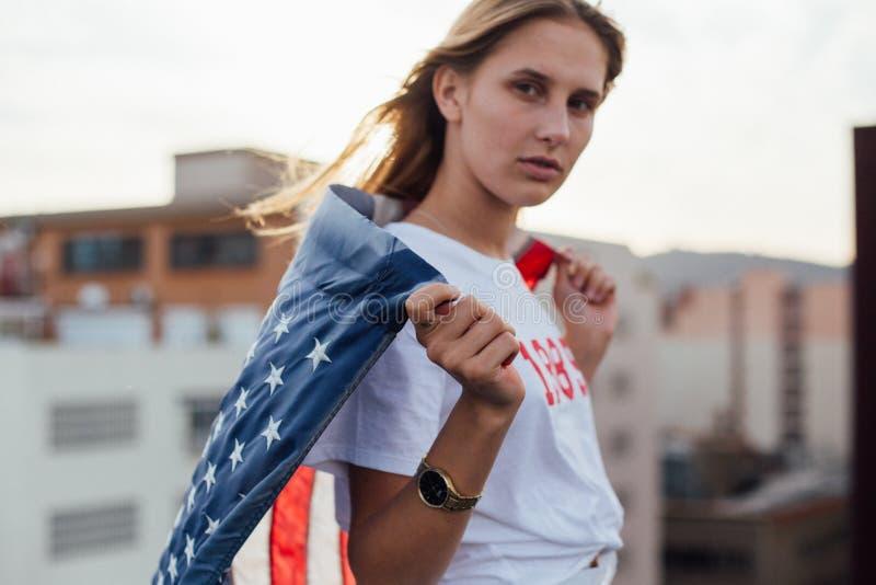 Den blonda kvinnliga modellen rymmer upp amerikanska flaggan royaltyfri foto