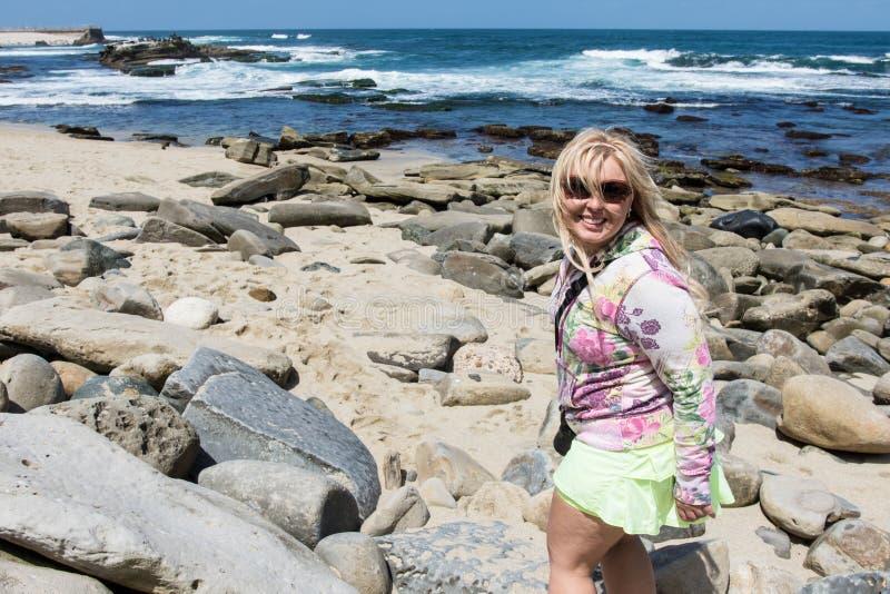 Den blonda kvinnlign undersöker kraftfullen, stenig strand av La Jolla Kalifornien royaltyfri bild