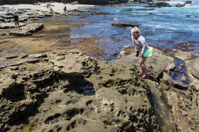 Den blonda kvinnlign undersöker kraftfullen, stenig strand av La Jolla Kalifornien under lågvatten arkivfoto