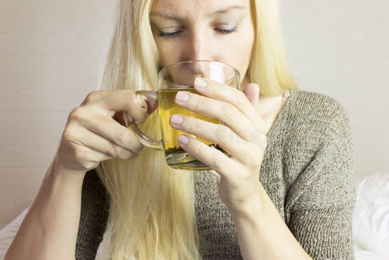 Den blonda longhaired kvinnan dricker varmt grönt te i genomskinlig kopp arkivbilder