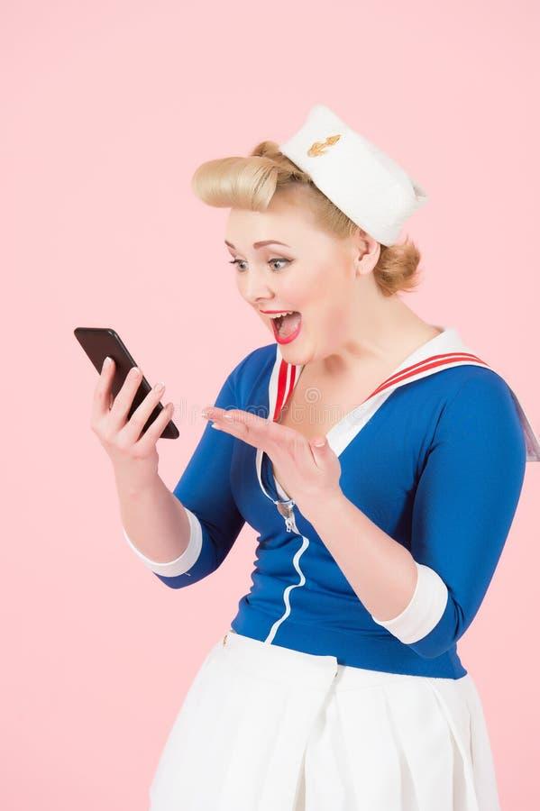 Den blonda lyckliga flickan mottog sms på hennes Smart-telefon anime klädde kvinnan som pratar med pojkvännen via cell- skriande  royaltyfria bilder