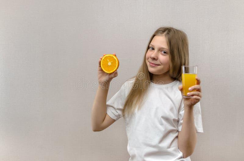 Den blonda lyckliga flickan rymmer i hennes hand ett exponeringsglas av ny fruktsaft banta sunt Veggie och strikt vegetarian arkivfoto