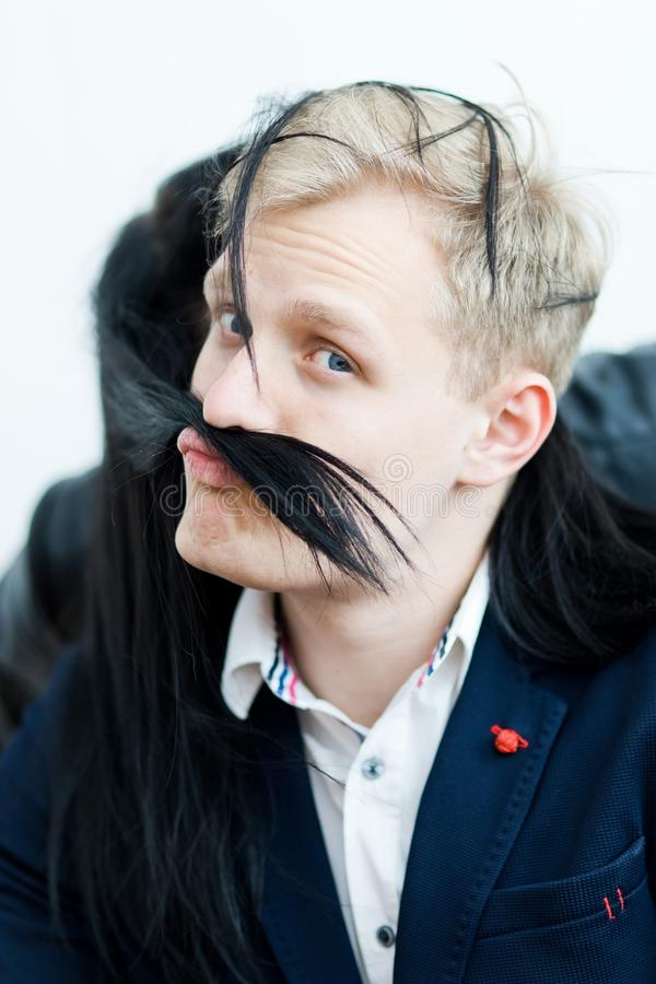 Den blonda mannen i formell klänning - fejka mustaschen från flickvännens hår royaltyfri fotografi