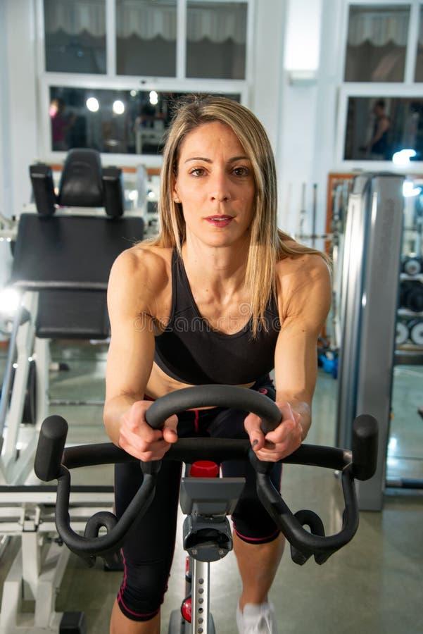Den blonda sportiga kvinnan övar i idrottshallen genom att använda motionscykelen arkivbilder