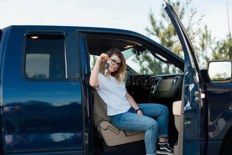 Den blonda tonåringen mottar en bil som gåva royaltyfri bild