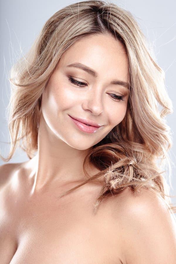 Den blonda unga kvinnan med sunt lockigt hår och naturliga utgör Härlig modellflicka med den krabba frisyren arkivfoto