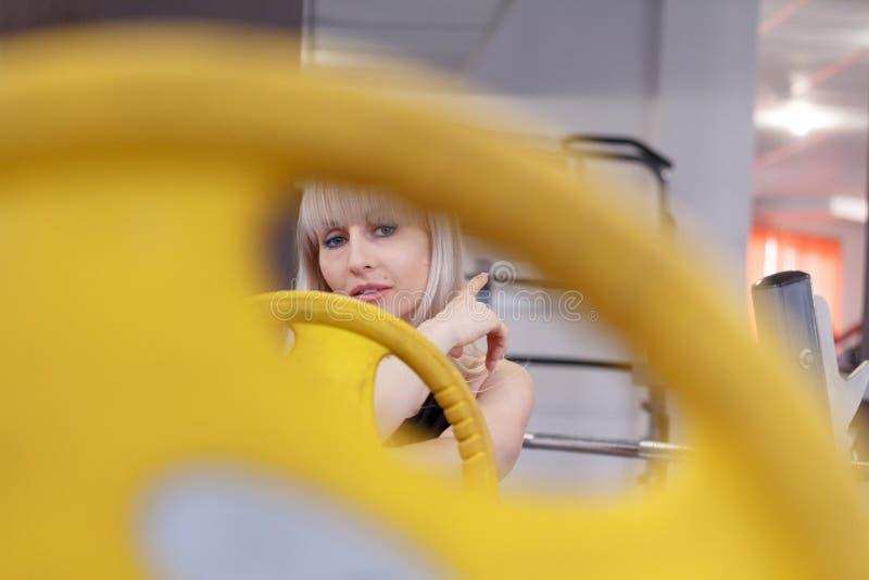 Den blonda unga kvinnan ser in i kameran till och med hål i en vikt för en skivstång, begreppet av ett sunt sportliv royaltyfria foton