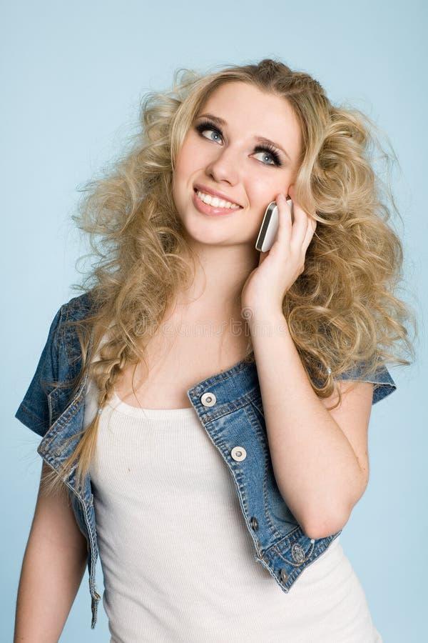 Den blonda unga kvinnan som talar på mobil, ringer. arkivbild