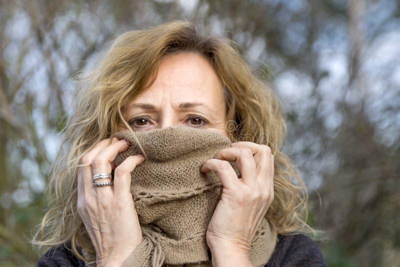 Den blonda vita kvinnan täcker hennes framsida med en beige ullhalsduk som lämnar endast ögonen avtäckade arkivbilder