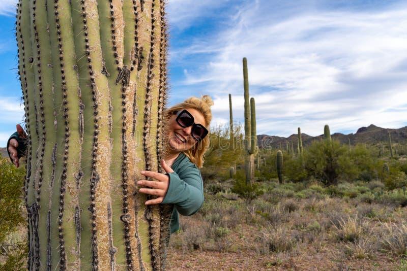 Den blonda vuxna kvinnan kramar en stor Saguarokaktus i den Arizona Sonoran öknen royaltyfri fotografi
