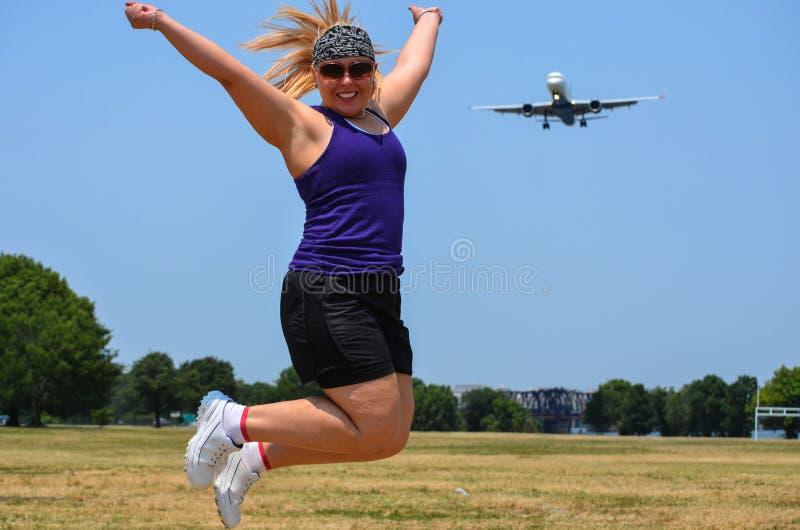 Den blonda vuxna kvinnan på grus- punkt parkerar i Washington DChopp som ett flygplan flyger in för en landning på DCAEN Reagan arkivfoton