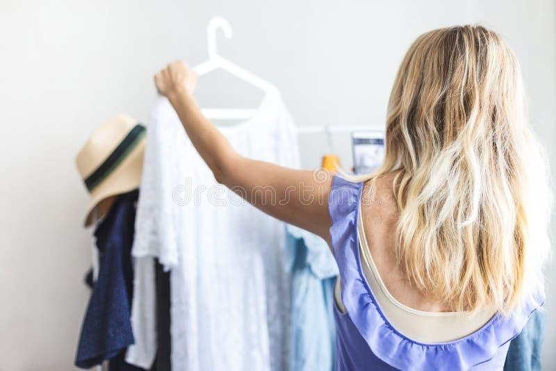 Den Blondy flickan nära en garderob med kläder kan inte välja vad för att bära royaltyfri fotografi
