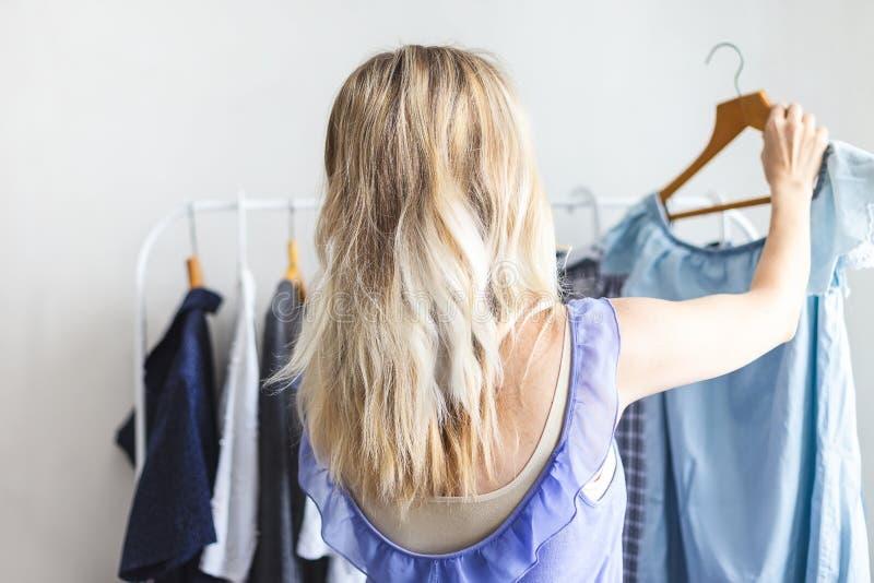 Den Blondy flickan nära en garderob med kläder kan inte välja vad för att bära arkivfoton