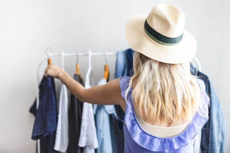 Den Blondy flickan nära en garderob med kläder kan inte välja vad för att bära royaltyfri bild