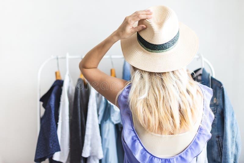 Den Blondy flickan nära en garderob med kläder kan inte välja vad för att bära royaltyfri foto