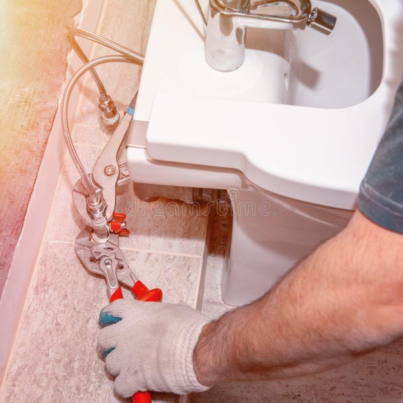 Den bostads- reparationen, byter ut ventilventilen, rörmokericloseupen, röd rörmokeriplattång för hand Närbildfast tillbehör för  royaltyfria foton